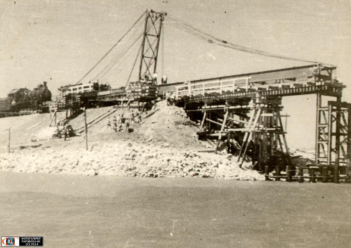 Апрель-1944 года: начало строительства моста через Керченский пролив. На снимке изображен момент установки первого металлического пролета краном-пилоном на западном берегу