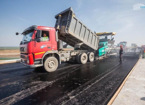 Строители уложили верхний слой асфальтобетона на пилотном участке Крымского моста на острове Тузла