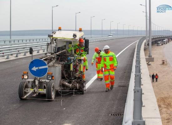 Строители наносят разметку на дорожное полотно моста через Керченский пролив